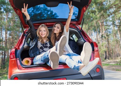 Young attractive woman sitting in the open trunk of a red car. Summer road trip