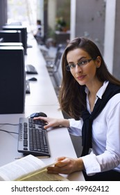 Young attractive woman sitting at PC in computer lab working and  studying a book.
