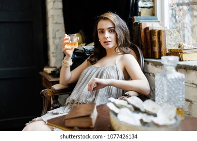 young attractive woman sitting in vintage armchair and holding glass of whiskey
