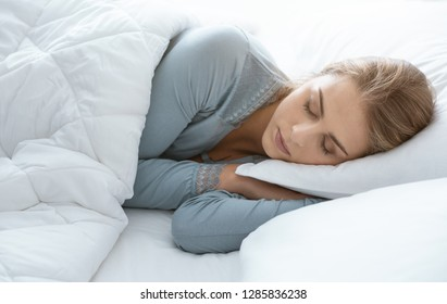Young attractive woman sleeping in the bedroom, she is lying on the side and relaxing with eyes closed