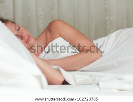 A young attractive woman sleeping on a bed with white sheets