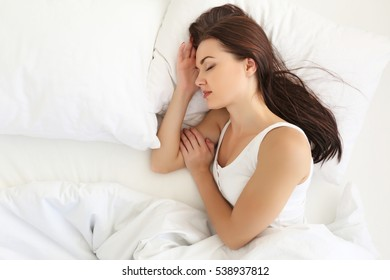Young attractive woman sleeping in white bed