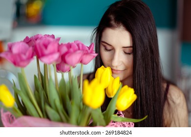 Young attractive woman smelling the pink and yellow tulips