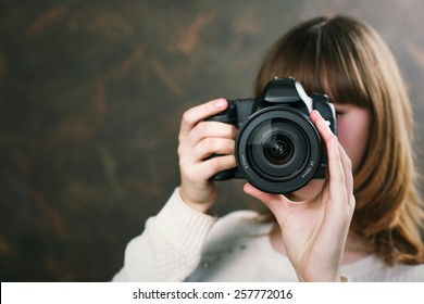 Young attractive woman smiling and holding a vintage camera