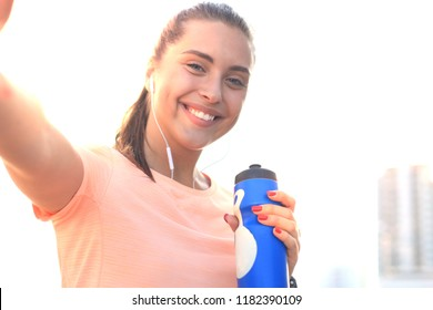 Young attractive woman in sports clothing looking at phone and smiling while taking selfie, during outdoors workout