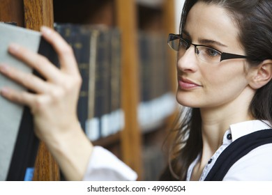 Young attractive woman standing at book shelf in old library pulling out a book.
