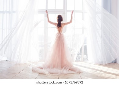 Young attractive woman standing by the window. Bride`s morning boudoir