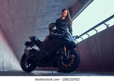 Young attractive woman is standing in tunnel with her bike and helmet.