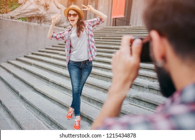 Young attractive woman stands on stairs and poses on camera. She keeps hands up and wears glasses with hat. Female touris is excited. Yong bearded man takes pictures of her.