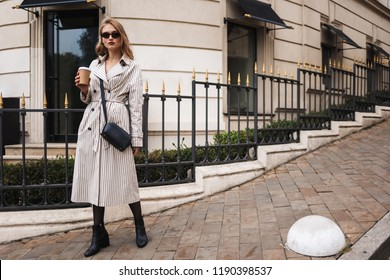 Young attractive woman in striped trench coat and sunglasses with little black cross bag holding coffee to go in hand thoughtfully looking in camera walking around city street