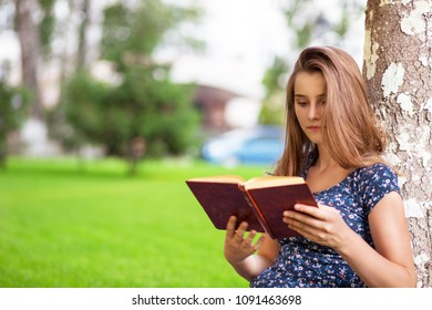Young attractive woman studying reading a book while sitting in campus on green lawn tree on background. Multicultural, mixed race, asian russian girl. Horizontal shot. People and literature concept