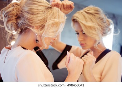 Young attractive woman, stylish. Attractive girl in evening dress, the reflection in the mirror in the background