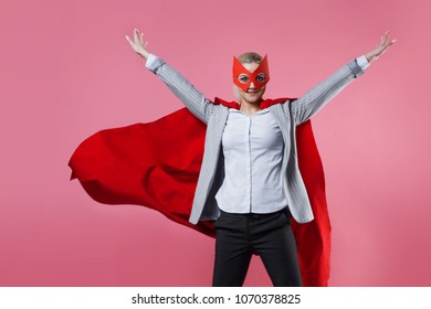Young attractive woman superhero. Girl in a business suit and a mask with red cloak of hero. On a pink background.