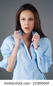Young attractive woman with surprised expression at grey background