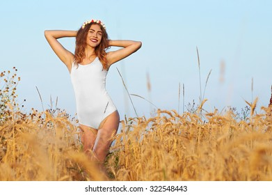 A young, attractive woman in swimsuit, posing in a field of flowers and wheat on a background of blue sky, hair, makeup, white corolla with flowers, model is looking at the camera, portrait.