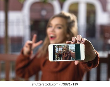 Young attractive woman take a photo on the smartphone in the cafeteria.