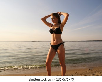 A young attractive woman with a tanned athletic body and beautiful Breasts in a black bikini on the beach against the background of water at the sunset of the autumn sun in September