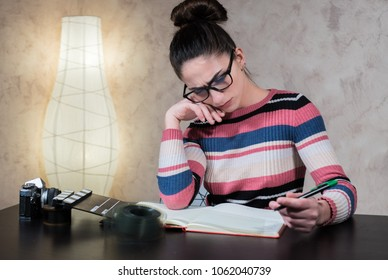Young attractive woman thoughtful working writing script with movie objects on desktop