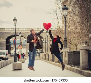 young attractive woman throwing a love heart shaped pillow to her boyfriend