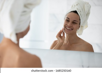 Young attractive woman with towel on head looking in mirror while cleanses skin using cotton pad and cosmetics product for properly deep clean, enjoy morning grooming routine after shower at bathroom