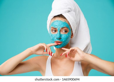 Young attractive woman with towel wrapped around her head applying colour face scrub mask. Daily routine - facial cleaning, skin care, peeling, moisturising and beauty treatment concept