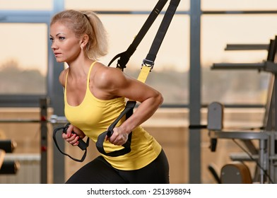 Young attractive woman training with htrx fitness straps in the gym's studio