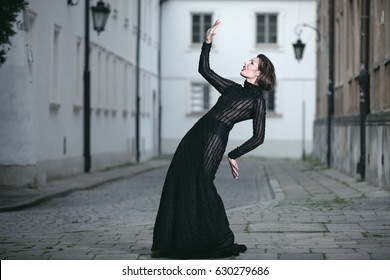 Young attractive woman in a trendy black dress posing on the street