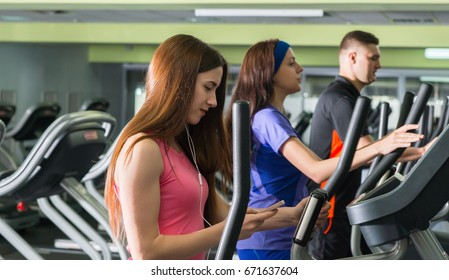 Young attractive woman turning on music while exercising on the crosstrainer machines in fitness center