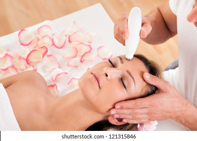 Young attractive woman undergoes microdermabrasion therapy in spa setting