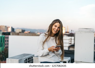 young attractive woman using her smartphone for make online shopping. female in a white sweater smiling. checking mobile phone. business woman looking at the screen. girl e-learning via her gadget