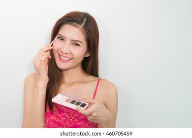 Young and attractive woman using mascara / photos of attractive young brunette woman on a white background .