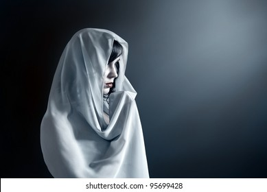 Young attractive woman in a veil prays on a dark background.