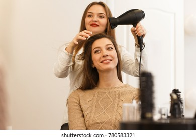 Young attractive woman visiting hairdresser. Woman in white shirt making hairstyle to a woman in beige sweater