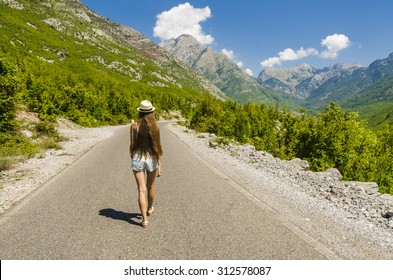 Young attractive woman walking along empty road