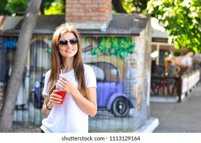 young attractive woman is walking around the city with a red cocktail (lemonade) in her hand