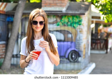 young attractive woman is walking around the city with a red cocktail lemonade in her hand