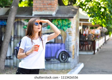 young attractive woman is walking around the city with a red cocktail lemonade in her hand and looking  into the distance