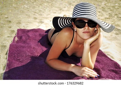 Young attractive woman wearing a black and white striped large beach hat, sunglasses and a black bikini laying  on the beach.