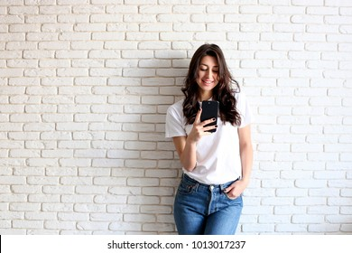 Young attractive woman wearing blank white t shirt receiving message on new cell phone. Pretty female model, smiling, holding mobile gadget in hands, messaging. Brick background, copy space, closeup