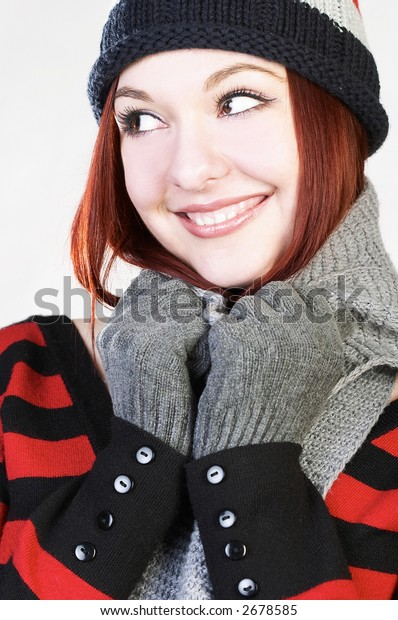 Young attractive woman wearing knit hat smiles and looks sidewards; isolated on grey.