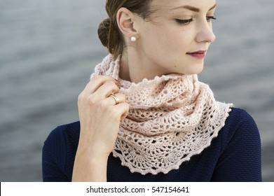 Young attractive woman wearing lacy crochet snood. Outdoor photography with river waters in background