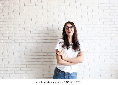 Young attractive woman wearing white shirt & cat eye glasses smiling wide. Pretty female model, hands crossed on chest, brunette hair posing. Girl, white brick wall background, copy space, closeup