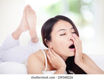 young attractive woman yawning in bed in the morning with nature green background, model is a asian girl