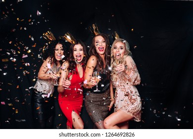 Young attractive women celebrating a party, drinking champagne and dancing. Sparkling confetti, having fun