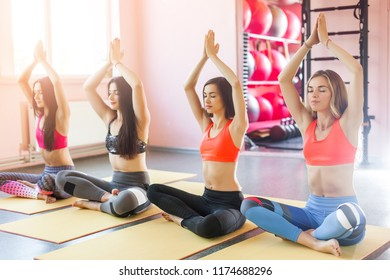 Young attractive women on yoga class. Group of beautiful girls making a relaxation exercise