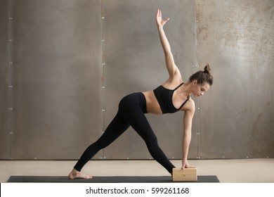 Young attractive yogi woman in black practicing yoga, standing in Utthita Trikonasana exercise using block, extended triangle pose, working out, cool urban style, full length, grey studio background