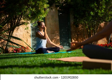 Young attractive yogi woman practicing yoga, using Alternate Nostril Breathing, making nadi shodhana pranayama therapeutic exercise, working out on green grass.