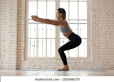 Young attractive yogi woman practicing fitness, doing bodyweight squat exercise, yoga chair pose, working out, wearing sportswear, black pants and top, indoor full length white yoga studio