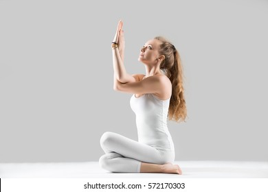 Young attractive yogi woman practicing yoga, sitting in Cow Face exercise, Gomukasana pose, working out, wearing sportswear, white tank top, pants, indoor full length, isolated, grey studio background