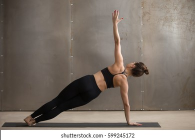 Young attractive yogi woman practicing yoga, standing in Side Plank exercise, Vasisthasana pose, working out, wearing black sportswear, cool urban style, full length, grey studio background, rear view